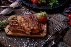 Piec na grillu warzywa na nieociosanym drewnianym stole i mięso Zdjęcia Stock