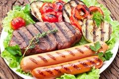 Piec na grillu warzywa nad zielonymi liśćmi na bielu talerzu na drewnianym stole i mięso fotografia stock