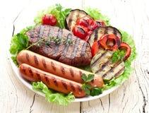Piec na grillu warzywa nad zielonymi liśćmi na bielu talerzu i mięso dalej zdjęcia royalty free