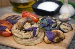 Piec na grillu warzywa z basilem na tnącej desce Zdjęcia Stock