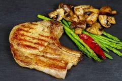 Piec na grillu wieprzowina stki z ziele, asparagus, pieczarki na kamieniu krytykują tło Fotografia Stock