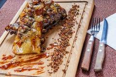 Piec na grillu wieprzowiny mięsa stek polędwicowy na drewnianym rozcięcie talerzu nad drewnianym stołem Zdjęcia Royalty Free
