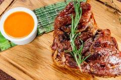 Piec na grillu wieprzowiny mięsa stek polędwicowy na drewnianym rozcięcie talerzu nad drewnianym stołem Fotografia Royalty Free