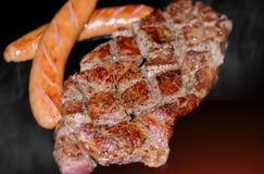 Piec na grillu wołowiien kiełbasy i stek zdjęcia royalty free