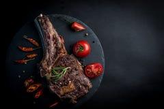 Piec na grillu wołowina stek na kości z pomidorami zdjęcie royalty free