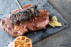 Piec na grillu wołowina stek polędwicowy z składnikami jak morza soli, pieprzu, cebuli i metalu listy na czerni desce, karmowy tł Obrazy Stock