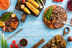 Piec na grillu wołowina stek z piec na grillu warzywami na drewnianym błękita stole Obrazy Royalty Free