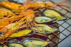 Piec na grillu zieleni mussels na węgiel drzewny kuchence przy nocy normą i garnele zdjęcia royalty free
