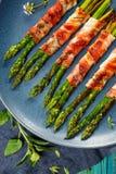 Piec na grillu zielony asparagus zawijający z bekonem na błękita talerzu Obraz Royalty Free