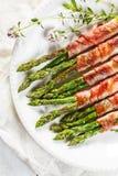 Piec na grillu zielony asparagus zawijający z bekonem na bielu talerzu Obrazy Royalty Free