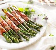 Piec na grillu zielony asparagus zawijający z bekonem na bielu talerzu Fotografia Stock