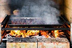Piec piec na grillu kasztany na grillu z płomieniami, ogieniem i cha, Fotografia Stock