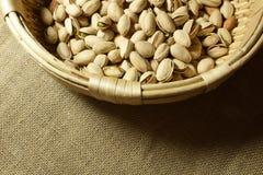 Piec pistacje na łozinowym koszu i grabić pod ciepłym światłem Zdjęcie Stock
