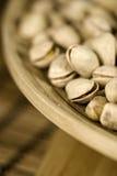 Piec pistacje w drewnianym pucharze Zdjęcia Stock
