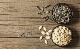 Piec słonecznikowi ziarna i dyniowi ziarna w brązie rzucają kulą na drewnianym stole obrazy royalty free