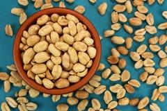 Piec solił arachidy w pucharze na błękitnym tle, odgórny widok Obrazy Royalty Free