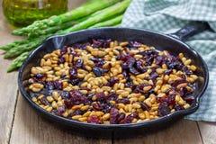 Piec sosnowe dokrętki z wysuszonymi cranberries Składniki dla zakąski z asparagusem Zdjęcia Stock