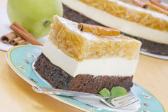 A piece of apple cake on a plate. A piece of an apple cake - grated apples in gelatine, light vanilla cream on chocolate pastry Royalty Free Stock Image