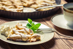 Piece of apple pie with cream on a plate. Closeup of piece of apple pie with cream on a plate Stock Image