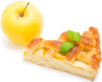 Piece of apple pie with fresh fruit. One slice of apple pie with  leaf of mint on top and yellow apple   on white background Stock Image