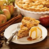 Piece of an apple pie with ice cream on a plate. Piece of an apple pie with ice cream scoop and caramel sauce on a plate, fall baking concept Stock Photos