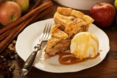Piece of an apple pie with ice cream on a plate. Piece of an apple pie with ice cream scoop and caramel sauce on a plate, fall baking concept Stock Image