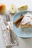 A piece of apple pie lying on blue plate, apple, cinnamon sticks Stock Photos