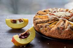 A piece of apple pie with quince, poppy seeds, raisins and sesame on the dark plate decorated with sliced fresh quince. On wooden brown table. Apple tart on Stock Images