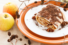 Piece of apple pie strewn grated chocolate and two fresh apples Royalty Free Stock Image