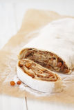 A piece of apple strudel on baking paper on a light  background Stock Photo