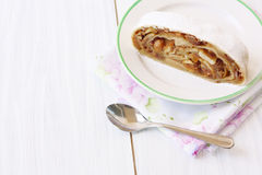 A piece of apple strudel on a plate on a light background Stock Photo
