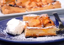 Apple tart with whipped cream and apricot glaze. Piece of an apple tart baked in puff pastry with an apricot glaze dusted in powdered sugar and served with fresh Stock Images