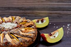A piece of apple tart with quince, poppy seeds, raisins and sesame on the dark plate. Apple pie decorated with sliced fresh quince. And sesame seeds on wooden Royalty Free Stock Photo