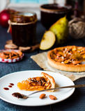 Piece of apple tart on a round plate, spoon caramel. French dessert Royalty Free Stock Image