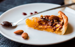 Piece of apple tart on a round plate, spoon caramel Royalty Free Stock Image