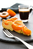 A piece of apricot cake on a black slate, two halves of an apricot, a cup of espresso. Yummy, fluffy apricot tart in the foreground. A glass of espresso in the stock photo