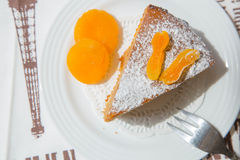 A piece of apricot pie on the white plate. A piece of apricot pie, decorated by dried apricots on the white plate. The dessert served on the table cloth with royalty free stock photos