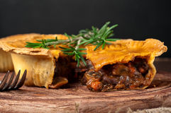 Piece of Australian meat pie with rosemary Stock Photos