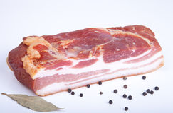 Piece of bacon, bell pepper and bay leaf on a light background Stock Photos