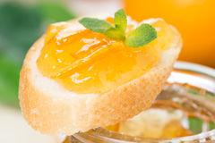 Piece of baguette with orange marmalade, close-up Stock Images