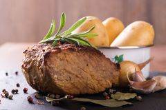 Piece of baked pork meat on slate stone. Horizontal photo of baked piece of pork meat with green rosemary herb on the top. Color pepper, bay leaf, onion, garlic Stock Photos