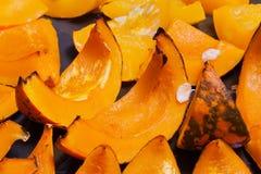 Piece of baked vivid orange colour pumpkin on the baking sheet Stock Photo