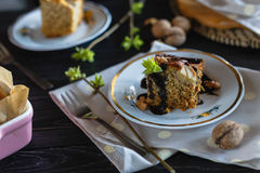 A piece of banana biscuit cake, poured with chocolate and decorated with walnuts and greens. Stock Photos