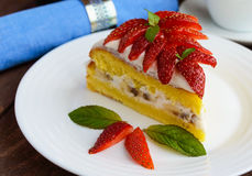 A piece of banana-strawberry sponge cake decorating with mint leaves on a white plate Stock Image
