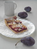 Piece of Bavarian plum pie on white plate with milk and fresh plums. Piece of Bavarian plum pie on white plate (with milk and fresh plums). Selective focus Royalty Free Stock Images