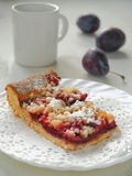 Piece of Bavarian plum pie on white plate with milk. Selective focus. Royalty Free Stock Images
