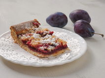 A piece of Bavarian plum pie on white plate. Selective focus Royalty Free Stock Images