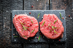 Piece of beef with rosemary and pepper on a stone plate Stock Images