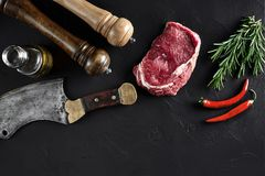 Piece of beef tenderloin, with ax for cutting and chopping meat, spices were cooking - rosemary, pepper on old black. Fresh raw meat. Beef steak. Piece of beef Stock Images