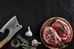 Piece of beef tenderloin, with ax for cutting and chopping meat, spices were cooking - rosemary, pepper, salt, garlic. Fresh raw meat. Beef. Piece of beef steak Stock Image